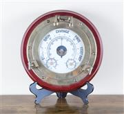 Sale 8489A - Lot 7 - A barometer in a brass ships porthole with mahogany frame, D 30cm