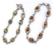Sale 9020 - Lot 326 - TWO SILVER GEMSET BRACELETS; one set with cabochon tigers - eye, other with peridots, length 19cm, wt. 30.34g.