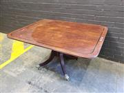 Sale 9014 - Lot 1093 - Late Georgian Mahogany Supper Table, the rectangular top with rounded corners & dark banding, on a pedestal with outswept feet & bra...