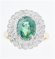 Sale 8502J - Lot 390 - AN 18CT GOLD EMERALD AND DIAMOND CLUSTER RING; featuring an oval cut emerald of approx 2.41ct, claw set above a double surround of 4...