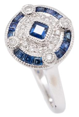 Sale 9149 - Lot 446 - A DECO INSPIRED SAPPHIRE AND DIAMOND RING; 9ct white gold disc plaque top centring a carre cut treated sapphire to double surround o...