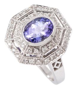 Sale 9149 - Lot 444 - A WHITE GOLD TANZANITE AND DIAMOND RING; octagonal top centring an oval cut tanzanite of approx. 1.46ct to double surround of round...