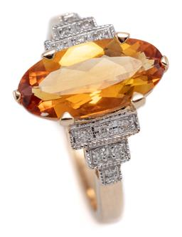 Sale 9149 - Lot 556 - A DECO STYLE 9CT GOLD CITRINE AND DIAMOND RING; centring a long oval cut citrine of approx. 2.50ct to tiered shoulders set with 12 r...