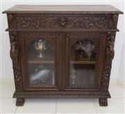Sale 8338A - Lot 61 - A late C19th Flemish carved dwarf bookcase, with a drawer, two arched glass doors and caryatids, on paw feet, H 106 x W 110 x D 49cm