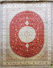 Sale 8634 - Lot 1025 - Large Silk and Wool Carpet, with rosette & pendants on a red oval field within a cream border (300 x 245cm)