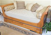 Sale 8470H - Lot 385 - A Bridget Forestier Cherrywood French style day bed with mattress and bolster cushions and concealed trundle bed, H 90 x L 215 x D 99cm
