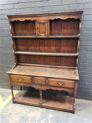 Sale 9014 - Lot 1007 - Georgian Style Oak Dresser, the rack top with central cupboard, above three drawers & turned legs, joined by an open shelf (h:180 x...