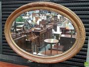 Sale 8562 - Lot 1040 - Early Gilt & Moulded Gesso Oval Mirror, with scroll-work to cardinal points & bevelled plate