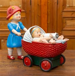 Sale 9160H - Lot 38 - A prop toy of a little girl pushing pram with baby doll, Height of girl 60cm x Length of pram 50cm  ex fox studio toy sale, prop...