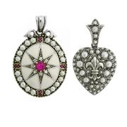 Sale 8253 - Lot 400 - TWO SILVER SEED PEARL PENDANTS; heart shape locket with fleur de lis design and oval pendant with white enamel and treated rubies.