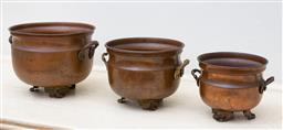 Sale 9190H - Lot 110 - A graduated set of 3 copper cauldron jardinières, each fitted with double brass handles and pierced bracket feet