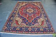 Sale 8390 - Lot 1037 - A Kashan Wool Carpet with blue medallion and boarder on red field (300 x 190cm).