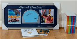 Sale 9165H - Lot 128 - A framed swimming cap signed by Grant Hackett featuring progress pictures and olympic memorabilia, Frame size 43cm x 93cm