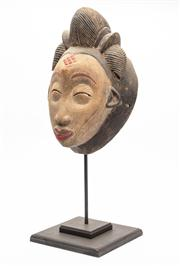 Sale 8844 - Lot 21 - An African Punu mask on stand, Gabon. Height of mask 32cm (total height 51cm including stand).