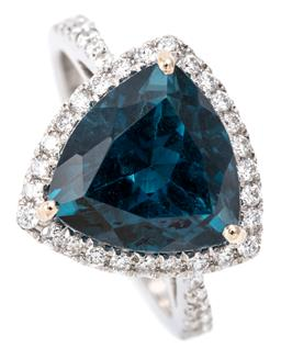 Sale 9132 - Lot 442 - AN 18CT WHITE GOLD TOPAZ AND DIAMOND RING; centring a trillion cut London blue topaz of 6.38ct to surround and shoulders set with ro...