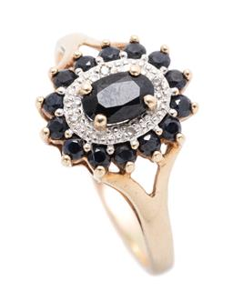 Sale 9253J - Lot 373 - A 9CT GOLD SAPPHIRE AND DIAMOND CLUSTER RING; centring an oval cut dark blue sapphire to surround of 4 round brilliant and single cu...