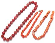 Sale 9083 - Lot 563 - THREE CORAL BEAD NECKLACES; a stand of 18.25mm round carved beads, length 65cm, a graduated strand of 10 - 15mm round beads, broken...