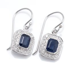 Sale 9253J - Lot 472 - A PAIR OF DECO STYLE SAPPHIRE AND DIAMOND EARRINGS; each earring centring an emerald cut blue sapphire to surround set with 18 round...