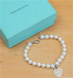 Sale 9165H - Lot 107 - A Tiffany and Co freshwater pearl bracelet and love heart charm (925), Length 19.5 cm, in original box.