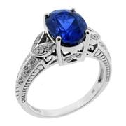 Sale 7995 - Lot 306 - A SYNTHETIC SAPPHIRE AND DIAMOND RING; four claw set in 9ct white gold with a synthetic verneuil sapphire of approx. 3ct, chip to gi...