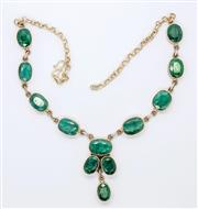 Sale 8265 - Lot 309 - A STERLING SILVER EMERALD NECKLACE; set with 12 oval cut opaque emeralds on a belcher chain with scroll clasp.
