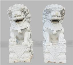 Sale 9215 - Lot 1037 - Pair of Carved Marble Dogs of Foo, one resting its paw on a pup, the other on a pierced ball, raised on lotus bases (h:152 w:55 d:82cm)