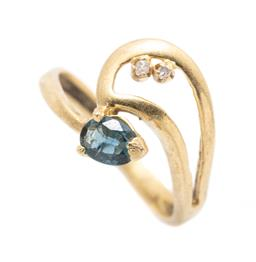 Sale 9253J - Lot 509 - AN 18CT GOLD SAPPHIRE AND DIAMOND RING; swirl design set with an oval cut blue green sapphire and 2 single cut diamonds (1 cracked),...