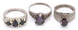 Sale 9164J - Lot 328 - THREE VINTAGE SILVER GEMSET RINGS; set across the top with 3 oval cut dark blue sapphires, one with an oval cut garnet above engrave...