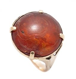 Sale 9253J - Lot 341 - A VINTAGE 9CT GOLD AMBER RING; set with a 17.4mm round cabochon amber (chipped) to stylised lotus shoulders, size N, wt. 4.39g.