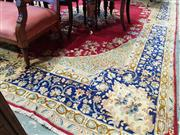 Sale 8792 - Lot 1089 - Mid 20th Century Kirman (Kerman) Wool Carpet, with blue central medallion on a madder ground & conforming floral border 383 x 268 cm