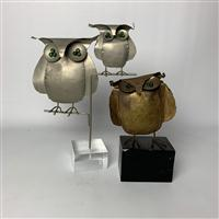 Sale 8725A - Lot 14 - Two brutalist modern owl sculptures with green glass eyes, one in brass effect on a painted timber base, the other in silvered tin o...