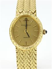 Sale 8655J - Lot 41 - AN 18CT GOLD BAUME AND MERCIER LADYS QUARTZ WRISTWATCH; oval gold dial with baton markers with cabochon sapphire crown, and integrat...