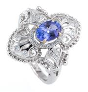 Sale 8915 - Lot 387 - AN 18CT WHITE GOLD TANZANITE AND DIAMOND RING; Edwardian inspired design centring an oval cut tanzanite of approx. 0.92ct to surroun...