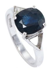 Sale 8928 - Lot 392 - AN 18CT WHITE GOLD SAPPHIRE AND DIAMOND RING; centring a blue oval sapphire of approx. 3.10ct adjacent to a triangle cut diamond of...