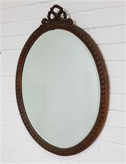 Sale 9215 - Lot 1061 - French Style Gilt Gesso Oval Mirror, with ribbon-and-staff border, surmounted by a ribbon (87 x 64cm)