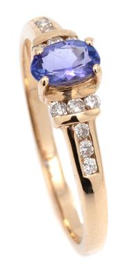 Sale 9090J - Lot 363 - A 14CT GOLD TANZANITE AND DIAMOND RING, centring an approx. 0.40ct oval cut tanzanite to shoulders channel set with 12 round brillia...
