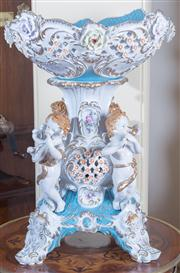 Sale 8430 - Lot 10 - A pair of rococo style porcelain centrepieces, the pierced bowl above four cherubs playing music. Height 52cm.