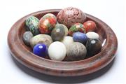 Sale 8673 - Lot 26 - A Collection of Mostly Stone and Crystal Eggs incl Tigerseye, Lapis in a Carved Timber Bowl