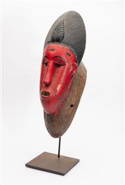 Sale 8844 - Lot 30 - An African (Ivory Coast) red painted and carved ceremonial  mask on stand. Height 40cm (total height 51cm including stand).