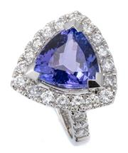 Sale 9066A - Lot 41 - A PLATINUM TANZANITE AND DIAMOND RING; corner claw set with a trilliant cut tanzanite of approx. 5.50ct to surround and shoulders se...