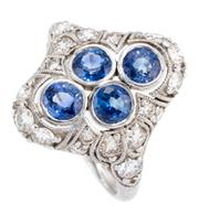 Sale 9066A - Lot 31 - A DECO STYLE PLATINUM SAPPHIRE AND DIAMOND RING; rub set with 4 round cut blue sapphires in a pierced surround and shoulders set wit...