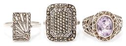 Sale 9149 - Lot 319 - THREE SILVER MARCASITE RINGS; rectangular plaque top with pierced radiant design, a pave set emerald shape plaque top, and one set w...