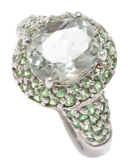 Sale 9156J - Lot 324 - A GREEN QUARTZ CLUSTER RING; set in silver with an oval cut pale green quartz to surround and shoulders set with further round cut q...