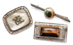 Sale 9164J - Lot 319 - THREE SILVER STONE SET BROOCHES; 40 x 21mm filigree set with rectangular cabochon tigers eye, 52mm long bar brooch collet set with...