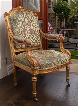 Sale 9160H - Lot 211 - A Louis XVI parcel gilt elbow chair upholstered in Boyac washed velvet fabric with floral design, the front legs raised on brass cas...