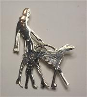 Sale 8036A - Lot 368 - A STERLING SILVER DECO STYLE BROOCH; featuring lady walking a large dog, 6.5 x 5cm