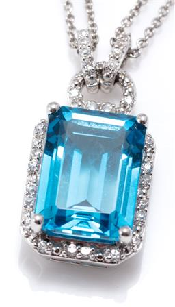 Sale 9156J - Lot 304 - A TOPAZ PENDANT NECKLACE; set in silver with an emerald cut blue topaz of approx. 8.60ct to surround and bale set with round cut whi...