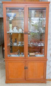 Sale 8346A - Lot 53 - A contemporary display cabinet with bevelled glass doors, sides and back atop a cupboard base revealing shelves, H 208 x W 105 x D 36
