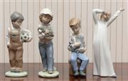 Sale 8881H - Lot 74 - Four Nao figures, one depicting a stretching child, a boy with football and two others with puppies. Height of tallest 20cm
