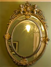 Sale 8418A - Lot 58 - An elaborate oval gilt cushion framed bevelled edge mirror, with cherubs holding a loft heraldic shield, with acanthus motif, H 136...